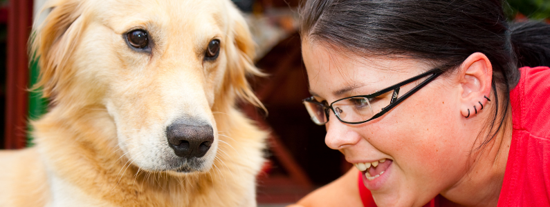 dark haired woman wearing glasses talk to her labrador