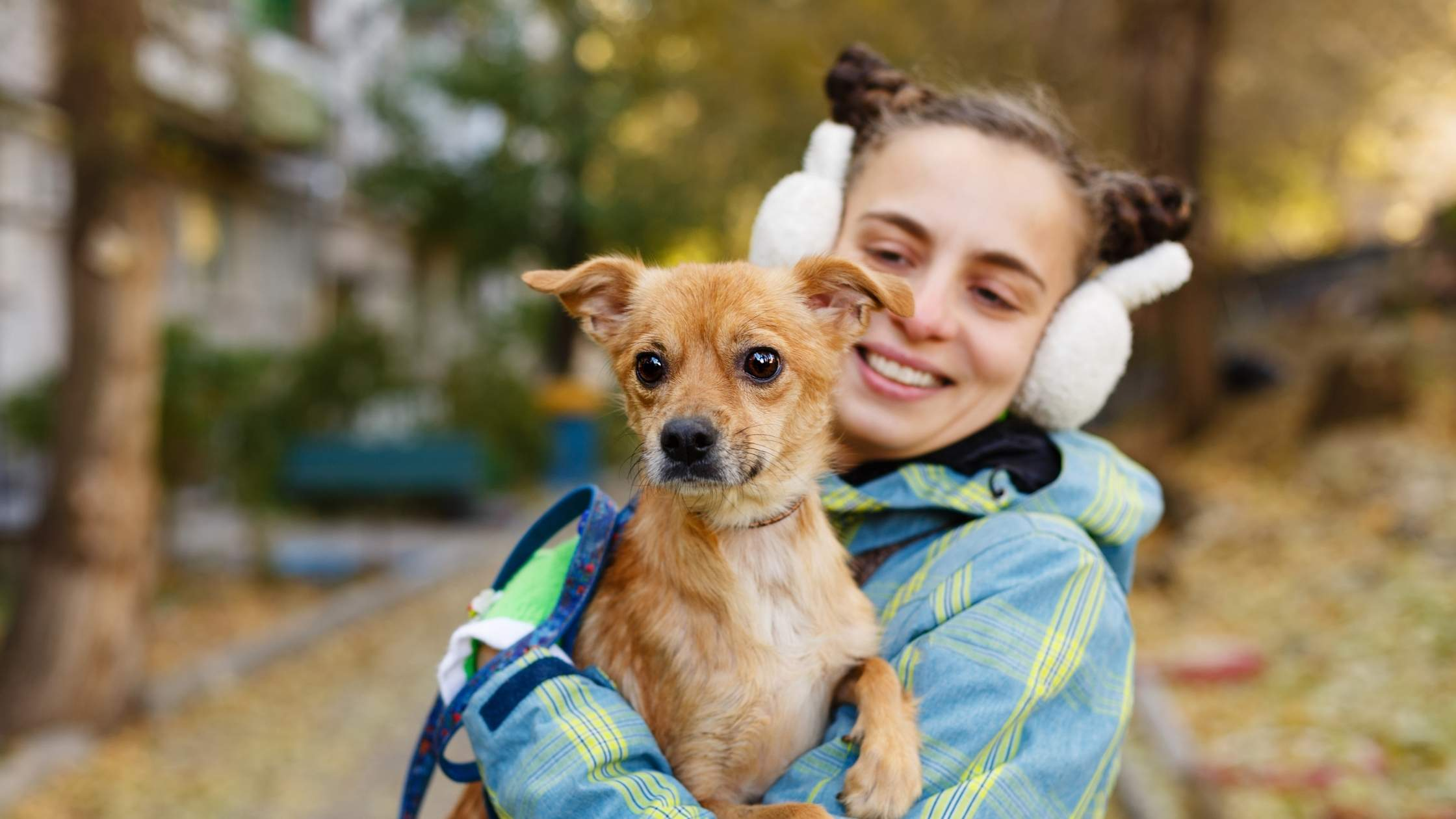 A young woman wearing white ear muffs smiles lovingly at the dog in her arms