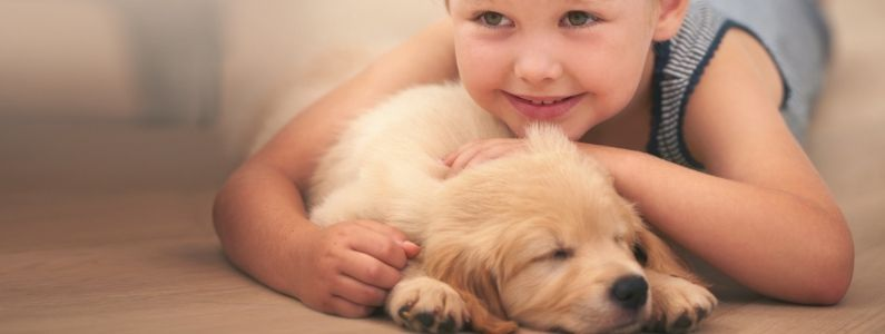 A blonde girls rests her head on a cute puppy
