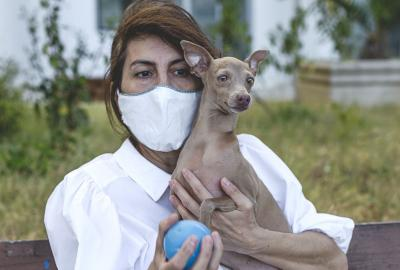 A brownhaired woman wearing a mask holds a small dog in one hand and a blue ball in the other