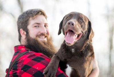 Bearded man in red checked shirt with smiling brown lab